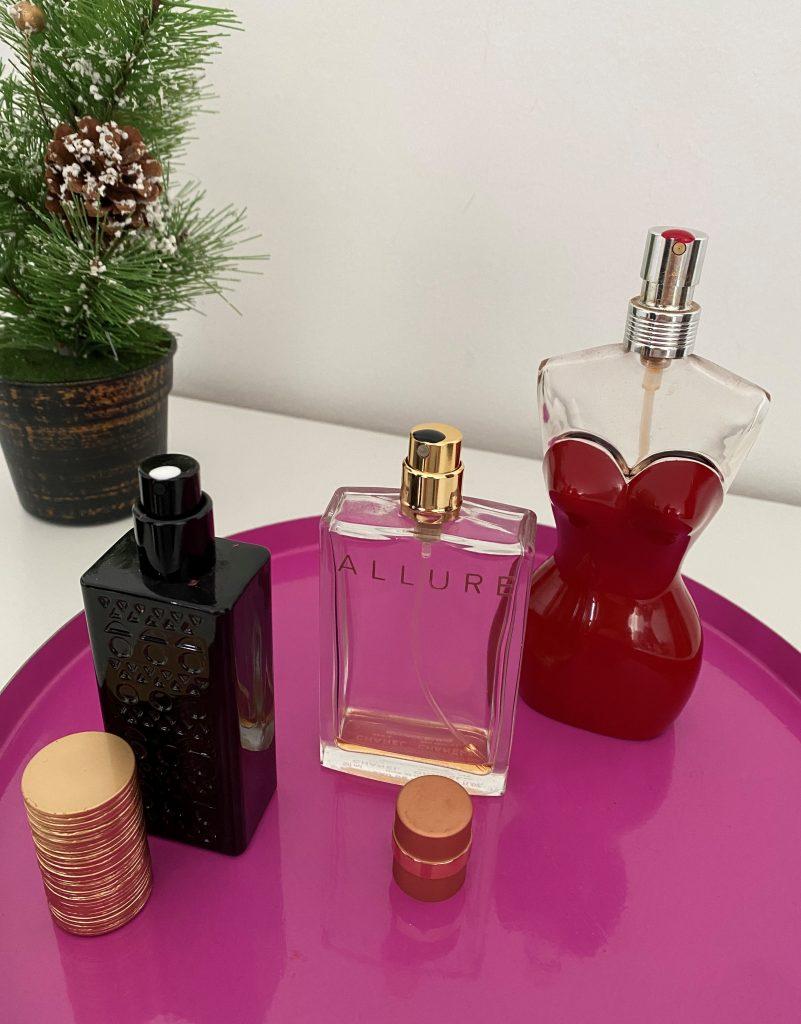 3 frascos de perfume de vários formatos, onde o pulverizador está assinalado com uma marca de verniz de cor contrastante.