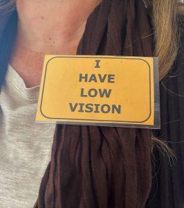 """Crachá ao peito amarelo com letras em preto, com o escrito: """"I have low vision"""""""