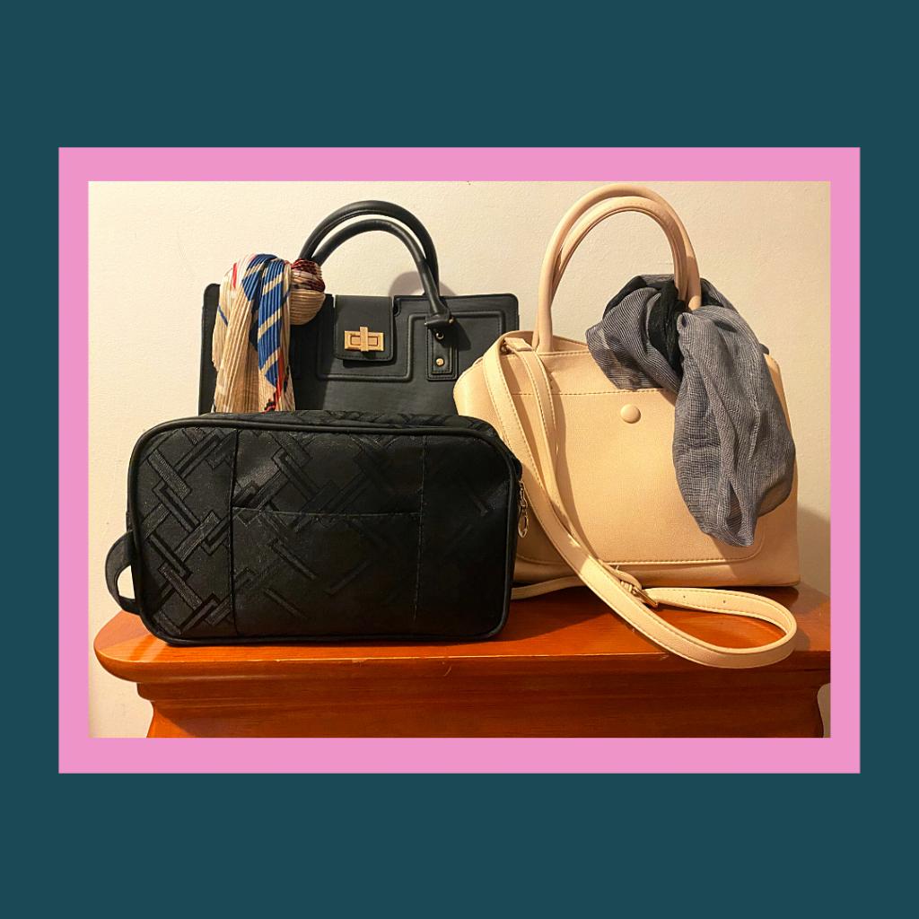 Duas malas, uma preta e uma bege com encharp de cor contrastante. A bolsa com os pertences.