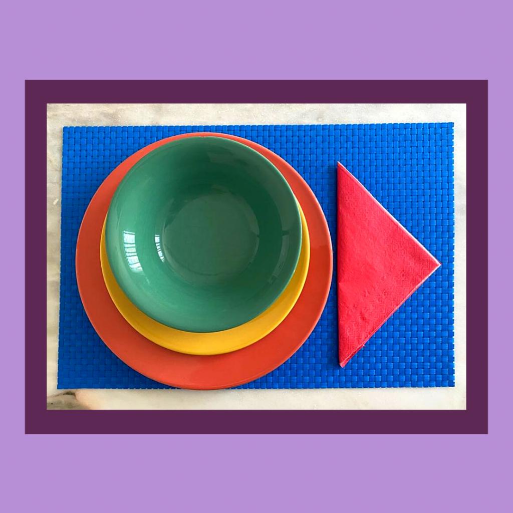 Base azul, prato raso rosa, sopa verde, sobremesa amarelo e guardanapo rosa.